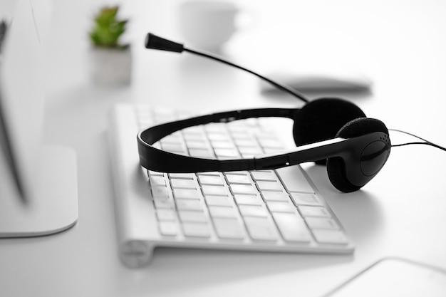 Kopfhörer liegt auf der computertastatur auf dem tisch im büro oder zu hause