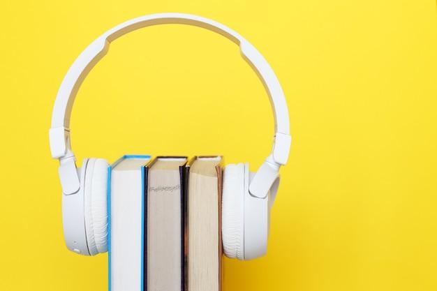 Kopfhörer mit buch auf gelbem grund