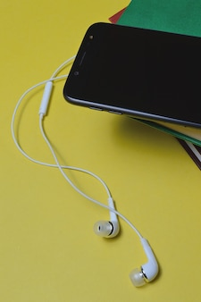 Kopfhörer mit büchern und einem smartphone auf gelbem hintergrund.