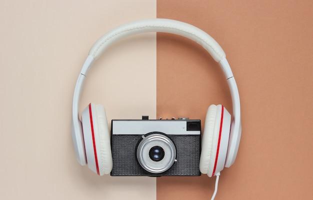 Kopfhörer mit einer retro-kamera auf einem braunbeigen hintergrund. draufsicht, minimalismus