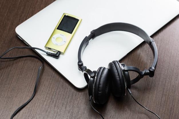 Kopfhörer mit laptop auf nahem hohem der tabelle