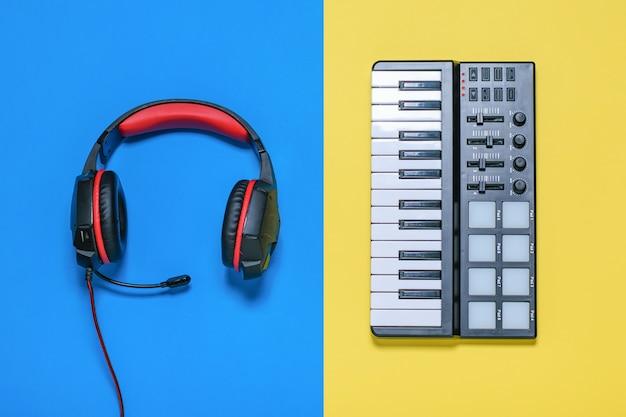 Kopfhörer mit mikrofon und kabeln und musikmixer auf gelbem und blauem tisch. der blick von oben.