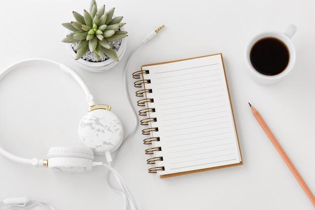 Kopfhörer mit notizbuch auf weißem schreibtisch