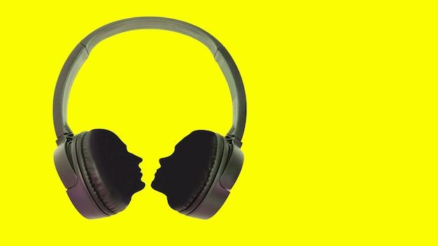 Kopfhörer mit silhouetten eines mannes und einer frau. konzept für design. isolierter gelber hintergrund. platz kopieren.