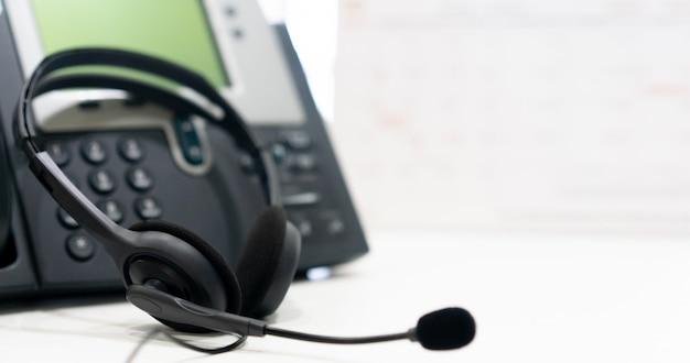 Kopfhörer mit telefongeräten am schreibtisch für kundendienst-stützkonzept