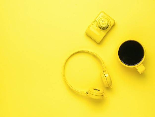 Kopfhörer ohne kabel, eine kamera und kaffee in gelb auf gelbem grund. farben-trend. platz für text.