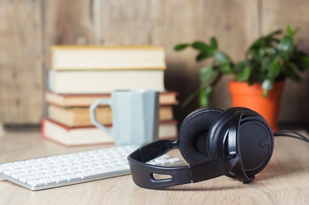 Kopfhörer, tastatur, stapel bücher und tasse auf dem schreibtisch. bürokonzept, arbeitstag, stundenlohn, arbeitszeitplan, arbeit in einem callcenter.