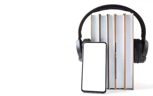 Kopfhörer, telefon und bücher auf weißem hintergrund. hörbuchkonzept.