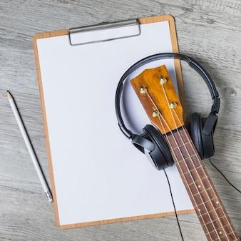 Kopfhörer über dem gitarrenspindelkasten über dem weißbuch auf klemmbrett mit bleistift