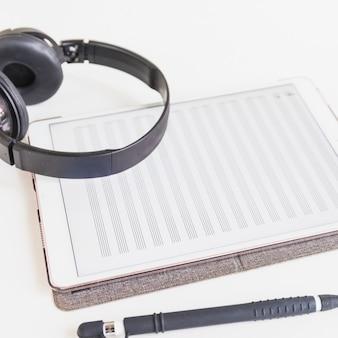 Kopfhörer über der grafischen digitalen tablette mit musiknote auf schirm mit schreibstift