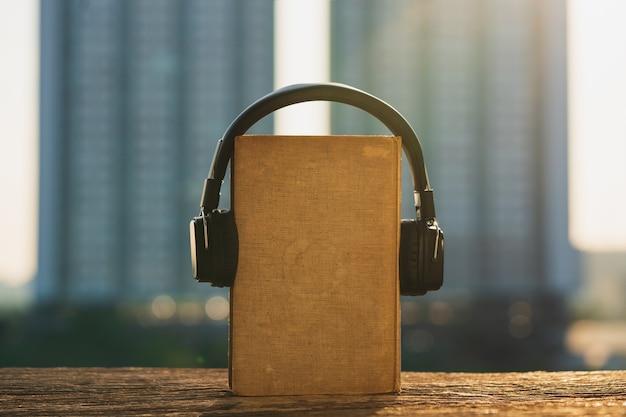 Kopfhörer und altes buch auf holz mit stadt