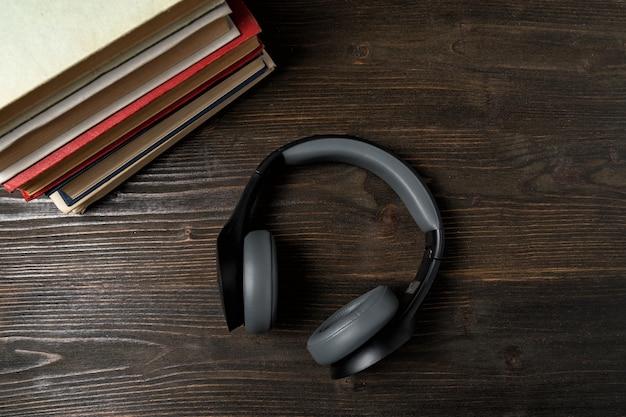 Kopfhörer und buch. audio-lernkonzept. dunkler hölzerner hintergrund. ansicht von oben