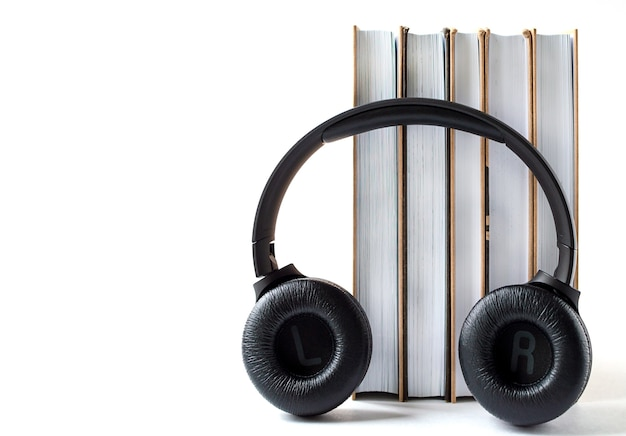Kopfhörer und bücher auf weißem hintergrund. hörbuchkonzept mit kopierraum.
