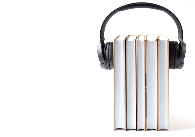 Kopfhörer und bücher auf weißem hintergrund. hörbuchkonzept.