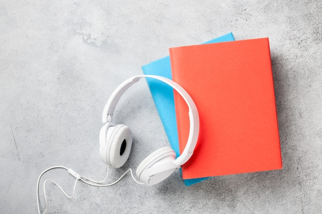 Kopfhörer und bücherstapel auf betonoberfläche