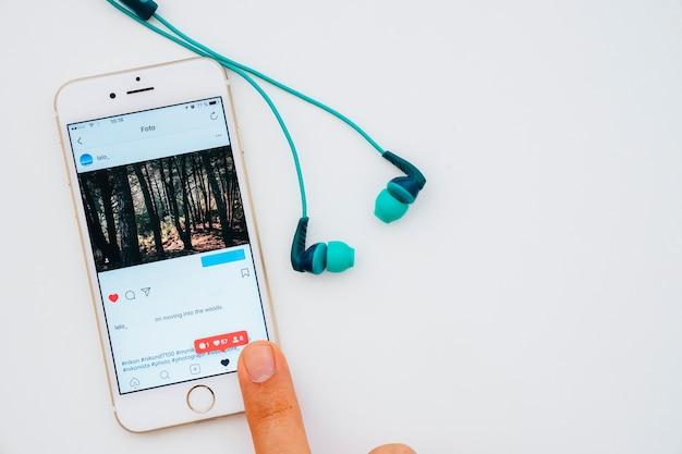 Kopfhörer und finger berühren telefon mit instagram