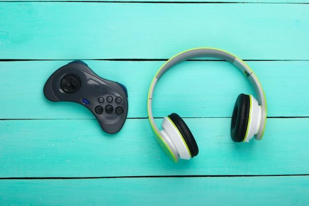 Kopfhörer und gamepad auf blauer holzoberfläche