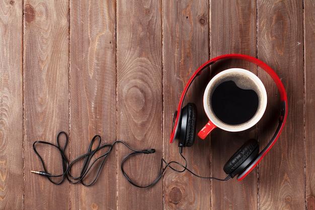 Kopfhörer und kaffeetasse auf schreibtisch aus holz. musikkonzept. draufsicht mit kopienraum