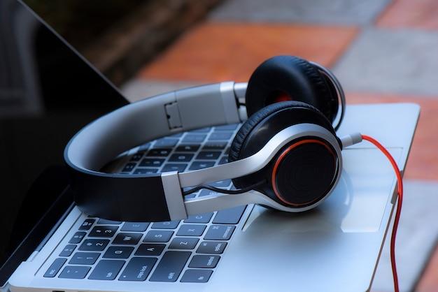 Kopfhörer und laptop auf weißer tabelle gegen defocused hintergrund