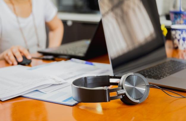 Kopfhörer und laptop-computertisch mit verschwommener frau, die vom hauptkonzept arbeitet.