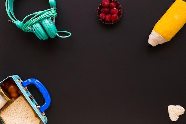 Kopfhörer und mäppchen in der nähe von lunchbox
