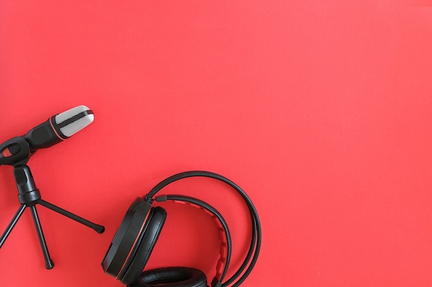 Kopfhörer und mikrofon auf rotem copyspace. konzeptmusik oder podcast. draufsicht, flache lage kopieren sie platz