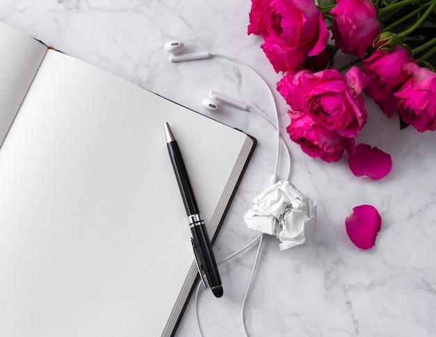 Kopfhörer- und rosenblumenstrauß mit leerem notizblock auf weiß