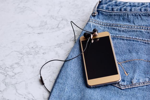 Kopfhörer und smartphone in der tasche von jeans, nahaufnahme