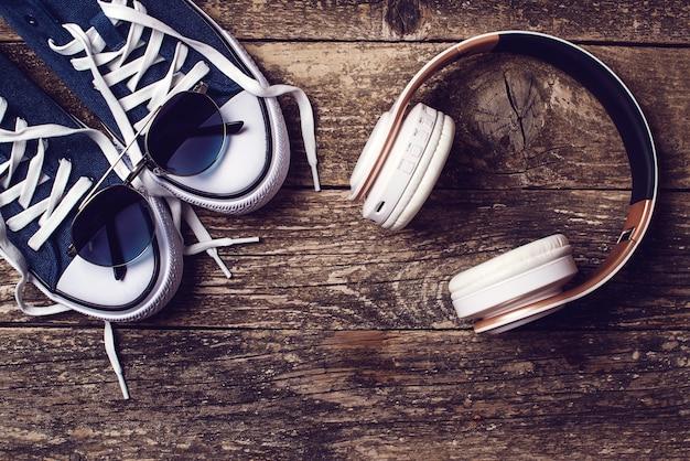 Kopfhörer und turnschuhe auf rustikalem hintergrund. satz trendige herrenaccessoires, draufsicht