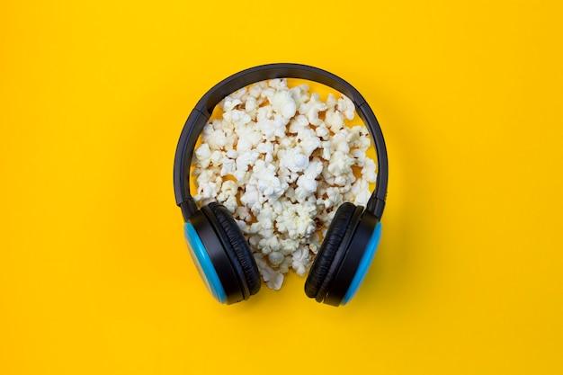 Kopfhörer und viel popcorn auf gelbem grund. videospielnachmittag