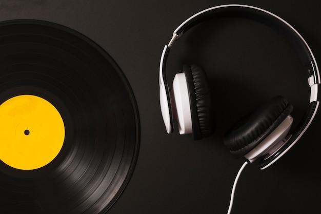 Kopfhörer- und weinlesevinylaufnahme auf schwarzem hintergrund