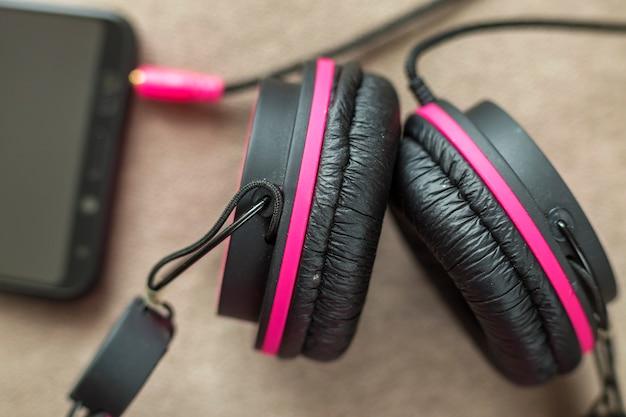 Kopfhörer verbunden mit handy isoliert auf hellem stoff flachen kopierraum hintergrund. moderne technologie, trendige unterhaltung, gadget-design und zubehörkonzept.