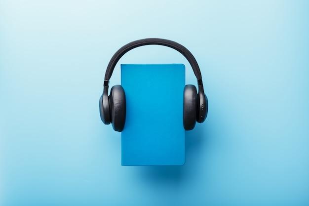 Kopfhörer werden auf einem buch in einem blauen hardcover auf einem blauen hintergrund, draufsicht getragen.