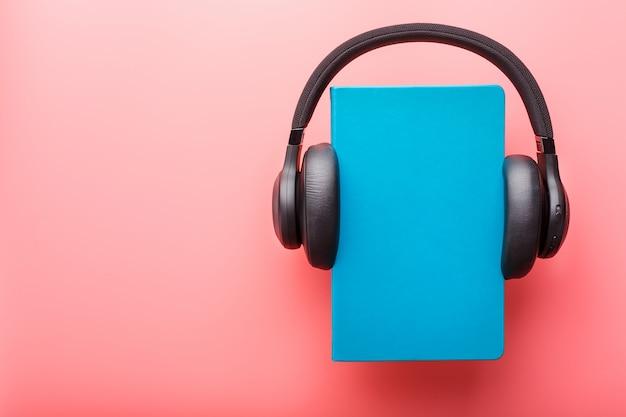 Kopfhörer werden auf einem buch in einem blauen hardcover auf einem rosa hintergrund, draufsicht getragen.