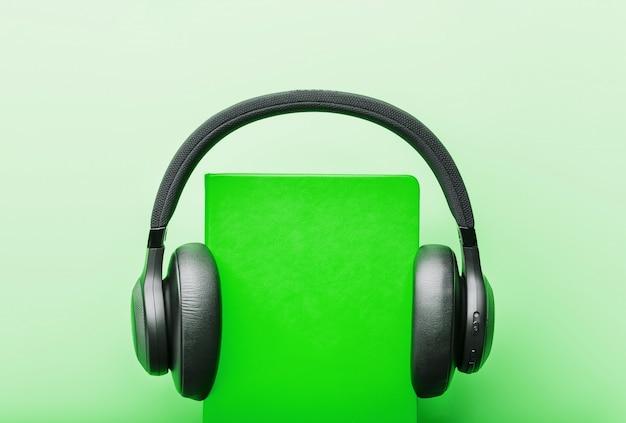 Kopfhörer werden auf einem buch in einem grünen hardcover auf einem grünen hintergrund, draufsicht getragen.
