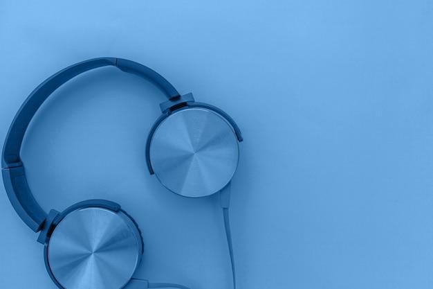 Kopfhörerfarben in der trendigen farbe des jahres 2020 classic blue hintergrund. helle makrofarbe. dj-kopfhörer mit dem kabel lokalisiert auf modischem buntem hintergrund, draufsicht der ebenenlage. musik.
