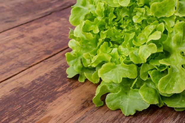 Kopfsalat, der auf einen braunen bretterboden gesetzt wird.