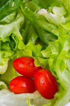 Kopfsalat mit kirschtomaten in der weißen untertasse auf einem holztisch