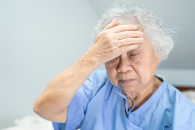 Kopfschmerz der asiatischen älteren fraupatienten beim sitzen auf dem bett im krankenhaus.