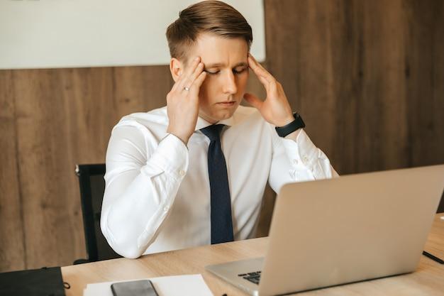 Kopfschmerzen, arbeitsbelastung, eine schwere aufgabe, ein mann, der an seinem arbeitsplatz müde ist. remote-arbeit an einem computer.