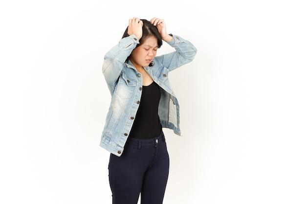 Kopfschmerzen der schönen asiatischen frau mit jeansjacke und schwarzem hemd isoliert auf weißem hintergrund