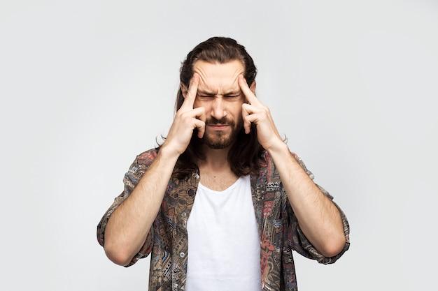 Kopfschmerzen, erkältungssymptom oder starke müdigkeit, migräne, chronische schmerzen. stilvoller sorgloser mann des hipster-reisenden auf einem weißen studiohintergrund, menschenlebensstil