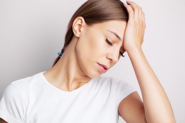 Kopfschmerzen, erschöpfte junge frau hat unter unerträglichen kopfschmerzen
