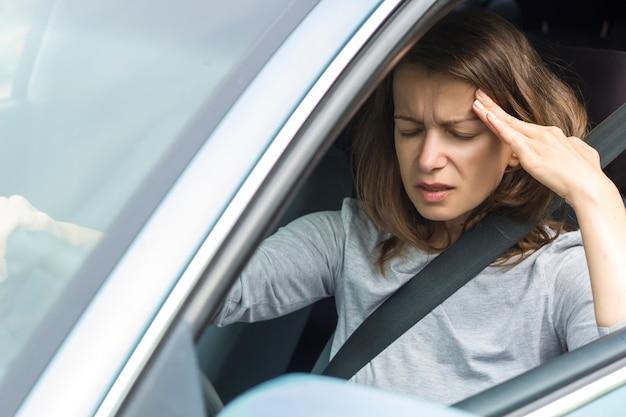 Kopfschmerzen in einer frau, die am steuer eines autos sitzt. schmerz im kopf des mädchens. ermüden.