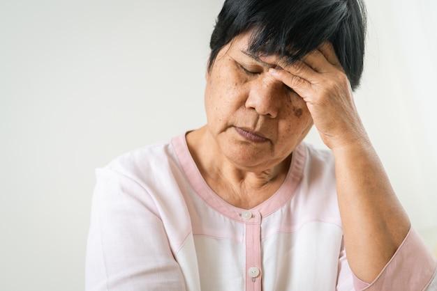 Kopfschmerzen, stress, migräne der alten frau, gesundheitsproblem des seniorenkonzepts