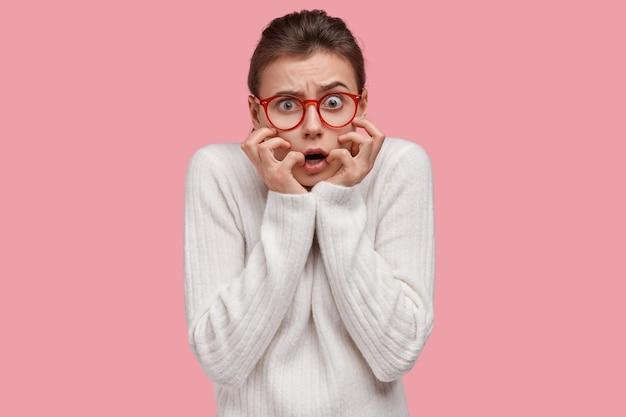 Kopfschuss der ängstlichen dunkelhaarigen jungen frau hält hände in der nähe des mundes, hat verlegenen ausdruck, sorgen vor wichtigem ereignis