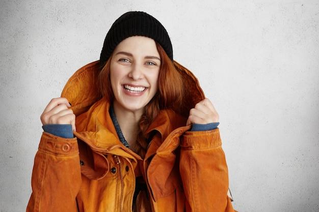 Kopfschuss der attraktiven jungen kaukasischen frau mit charmantem lächeln, das trendige winterkleidung trägt