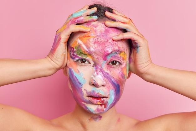 Kopfschuss der ernsthaften brünetten asiatischen frau hält hände auf kopf schaut direkt auf kamera verschmiert mit farben posiert mit nackten schultern vor rosa hintergrund