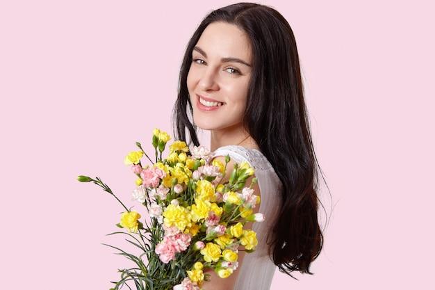 Kopfschuss der hübschen europäischen jungen frau mit zartem lächeln, gesunder haut, dunklem langem haar, trägt blumenstrauß der frühlingsblumen