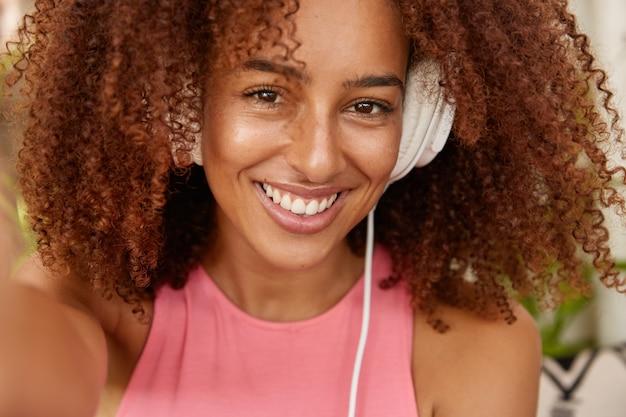 Kopfschuss der hübschen lächelnden frau hat charmantes angenehmes lächeln
